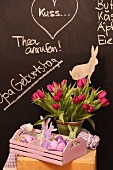 Vase of tulips and Easter ornaments in wooden tray against chalkboard wall with messages in chalk
