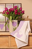 Hand-made tea towel with Easter motif and vase of tulips