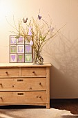 Easter arrangement and framed fabric hearts on top of chest of drawers