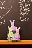 Dyed Easter eggs in egg box and hand-sewn egg cosies against chalkboard wall