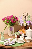 Easter place setting, vase of tulips and pastries and Easter ornaments on cake stand on wooden table