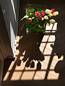 Bouquet of tulips in glass vase casting a shadow on the wooden floor
