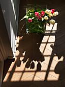 Strauß Tulpen in der Glasvase wirft Schatten auf den Holzboden