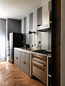 Grey and white striped wall in kitchen with free-standing elements