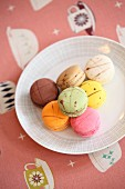 Plate of colourful macarons on tablecloth with pattern of coffee cups