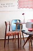 Various retro chairs around Gerbera, meringue and sugar bowl on table