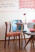 Verschiedene Retro Stühle um Tisch mit Gerbera, Schaumgebäck und Zuckerdose
