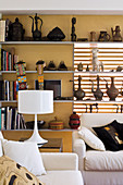 Various collections on wall-mounted shelves, white table lamp on side table and sofa set