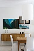 Pictures on wall above retro sideboard behind rustic dining table and loose-covered chairs