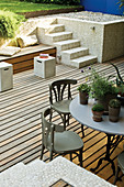 Table and chairs on wooden terrace with steps leading to garden