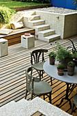 Tisch und Stühle auf Holzterrasse, Treppe führt zu dem Garten
