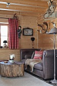 Sofa and tree-stump table on castors in corner of room in wooden cabin