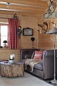 Sofa und rollbarer Baumstamm-Tisch in Zimmerecke einer Holzhütte