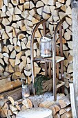 Old wooden sledge used as shelves in front of stacked firewood