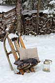 Old wooden sledge used as Viking chair in snowy garden