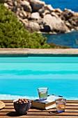 Buch und Gläser auf Holzablage vor Swimmingpool mit Blick auf Küste und Meer