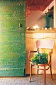 Retro chair on terrazzo floor next to green studded door