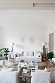 White loose-covered furniture and coffee table in shabby-chic living area