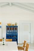 White dining room with traditional blue cupboard