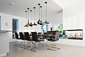 Various black pendant lamps above elegant dining table and chairs in designer apartment