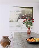 Roter Rosenstrauss vor Gemälde auf Tisch