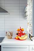 Rote Etagere mit Früchten auf weisser Küchenarbeitsplatte