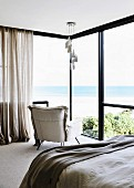Designer lamp and armchair in the bedroom in front of a window with sea view