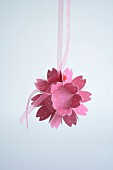 Pink paper flower hung from ribbon