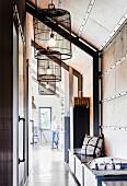 Sitztruhe mit Kissen und Vintage Käfige als Lampenschirme in loftartiger Wohnung
