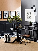 Round table, zebra-style pouf, leather folding chair, console table in front of black wall, black and white pictures in the background over black cassette cladding