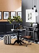 Runder Tisch, Pouf in Zebra-Look, Leder-Klappstuhl, Konsolentisch vor schwarzer Wand, im Hintergrund schwarz-weisse Bilder über schwarzer Kassettenverkleidung