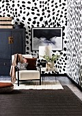 Upholstered chair, side table and Chinese cupboard in the living room with Dalmatian wallpaper