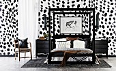 Double bed with black frame and black nightstand against wall with Dalmatian wallpaper