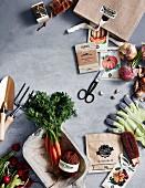 Frisches Gemüse, Gemüsesamen in Tütchen und Gartenwerkzeuge auf grauem Untergrund