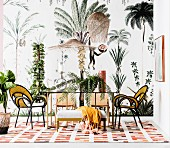 Dining table with glass top and designer chairs in front of wallpaper with plant and animal motifs