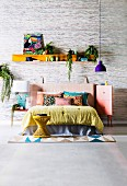 Colorful blanket and pillows on bed with leather headboard, pendant lamp with purple lampshade and shelf with picture and house plants against wallpaper