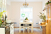 Festively decorated kitchen-dining room with diamond-patterned wallpaper