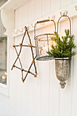 Star made from twigs, candle lantern and conifer sprigs hung from pegs