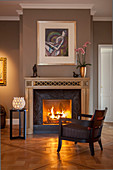 Upholstered armchair in front of roaring fire in open fireplace