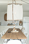 Large ceiling lamp above long dining table in open-plan kitchen