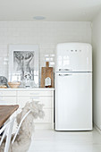 Retro fridge in white kitchen with wooden accessories