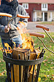 Grilling sausages on sticks over fire in brazier