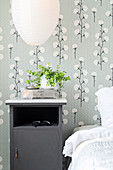 Grey bedside cabinet against wallpaper with pattern of cotton plants