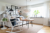 White furniture, gallery of pictures and rocking chair in bright living room