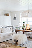 Sheepskin on stool in front of sofa in white living room