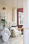 Sheepskin on rattan armchair and lanterns on veranda