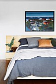 Double bed with various pillows under a black framed painting
