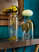 Glass covers over sycamore leaves on console table