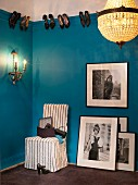 Large black and white photos, easy chair, sconce lamp and chandelier in cloakroom with shoes hung on picture rail on blue walls