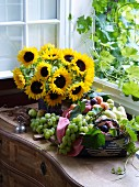 Opulent fruit bowl and vase of sunflowers next to window